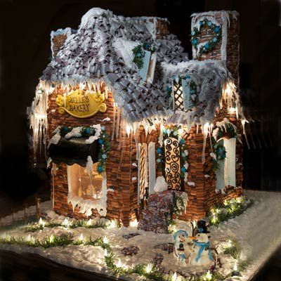 A gingerbread house with bright lighting placed around the house and on the icicles.