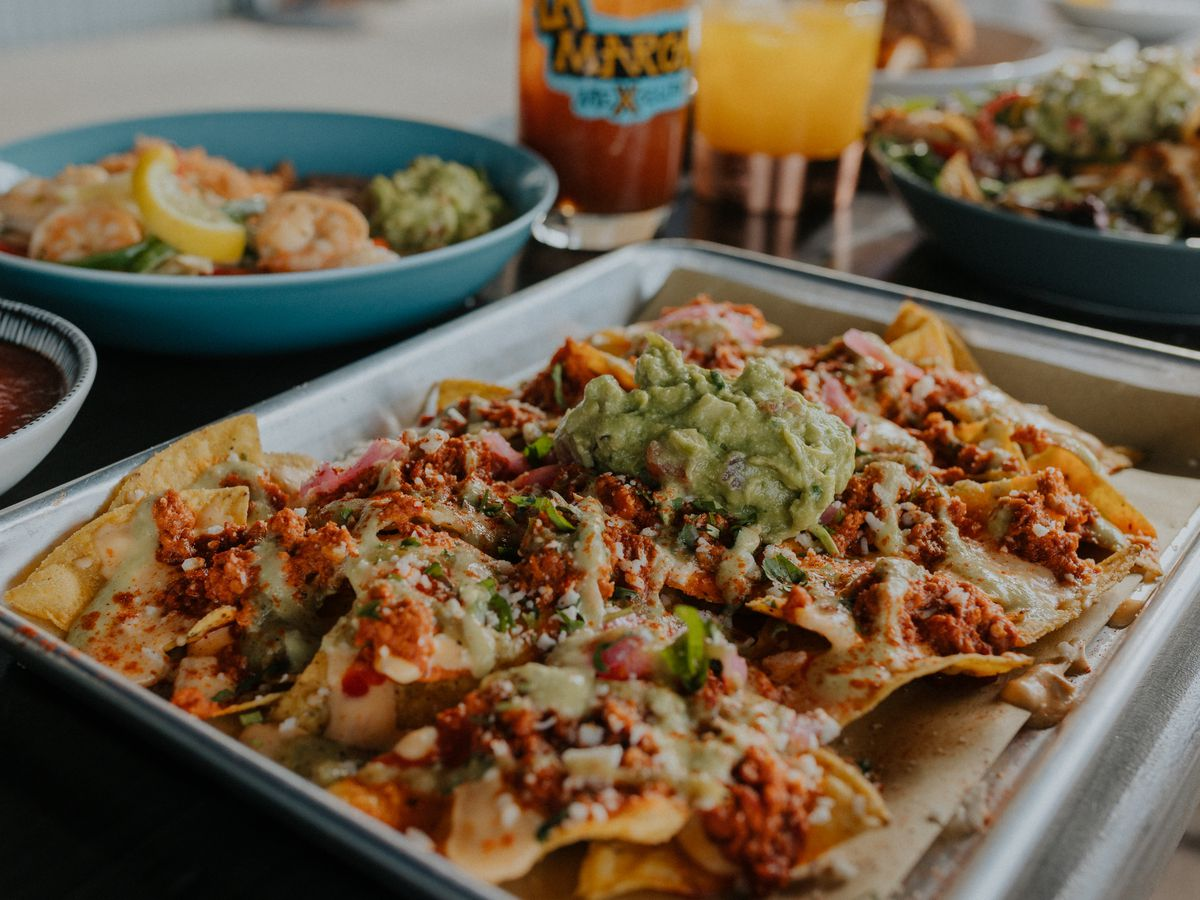 A metal tray of nachos pilled with salsa and avocado, beside other blurred out dishes and drinks
