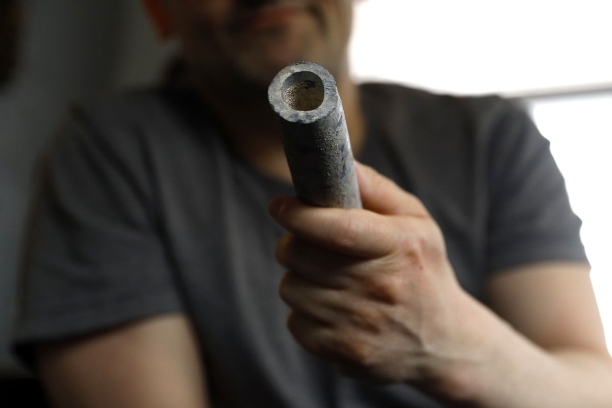 Troy Hernandez, an environmental justice activist, shows a piece of lead pipe obtained from his residence in Pilsen in April.