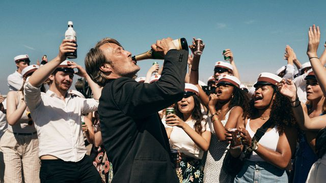 a crowd cheers on mads mikkelsen as he drinks from a bottle