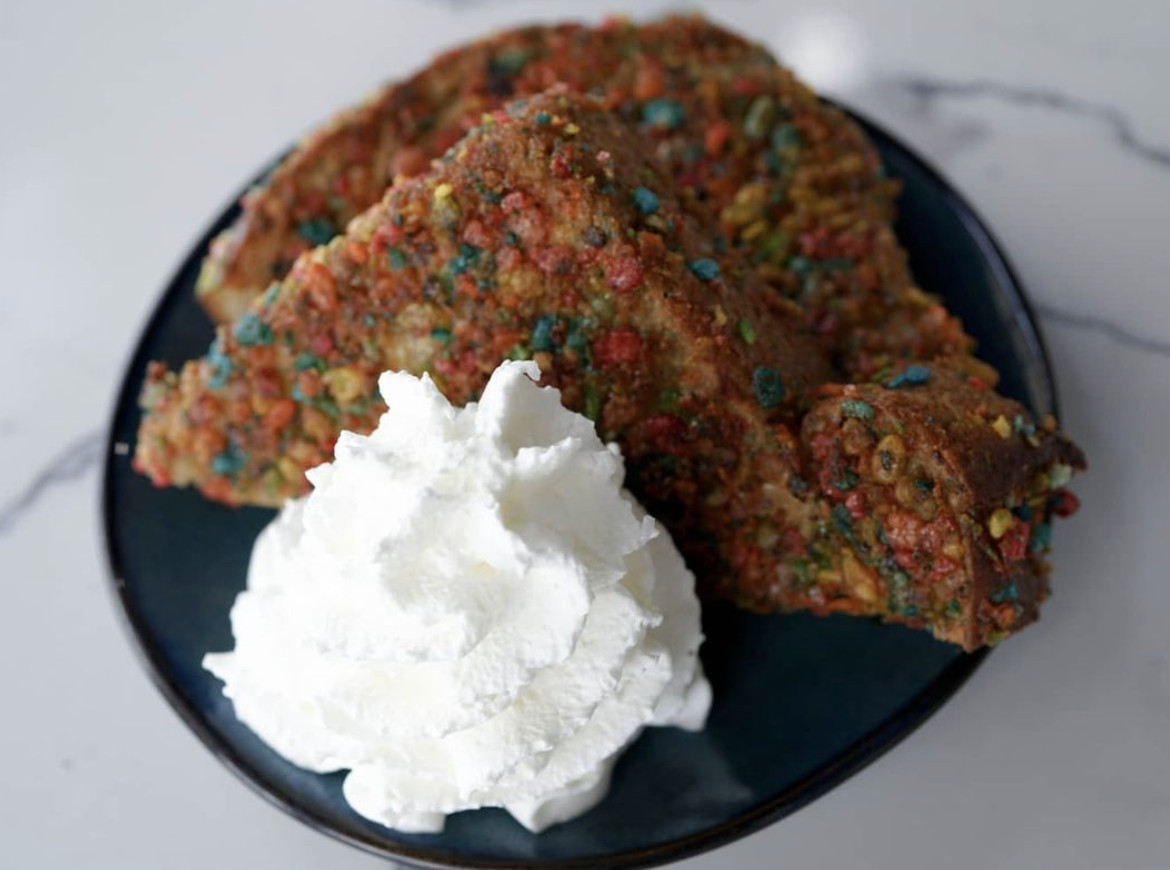 French toast crusted with Fruity Pebbles next to a dollop of whipped cream