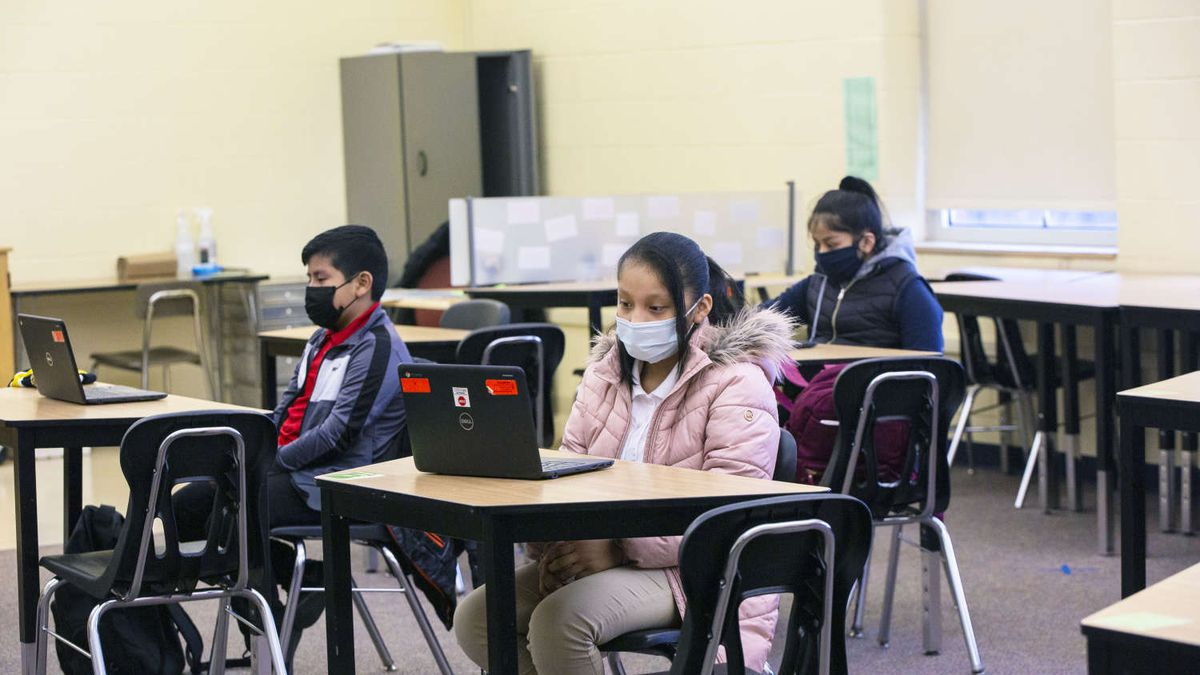 Students sit at desks, masked and distanced, on first day of in person learning