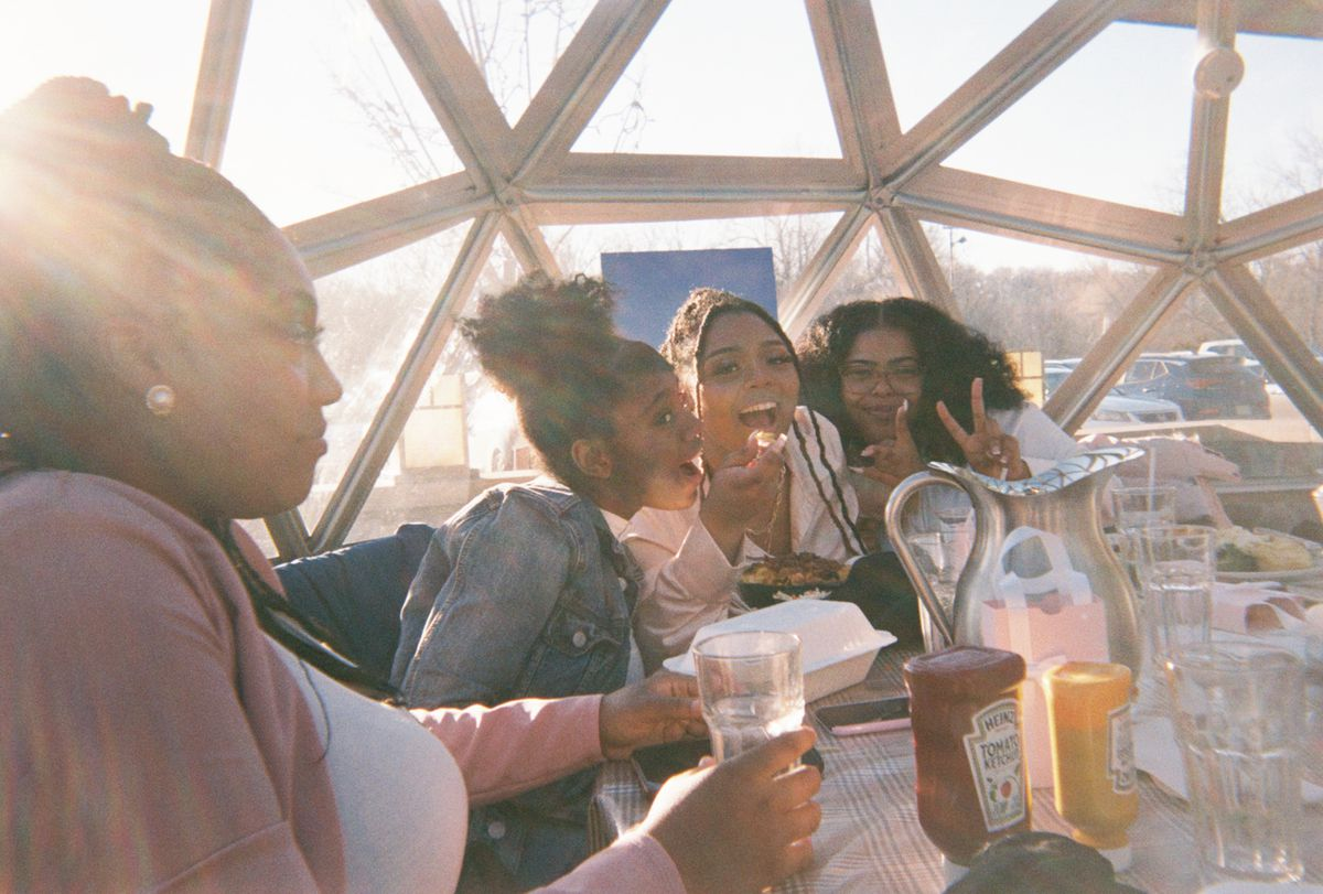 A group of young women pose together with their food at a restaurant table, with sunlight cascading in behind them.