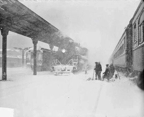 Image ofsnowstorm scene at LaSalle Street depot inChicago,Illinois. On the right, train cars are stopped at the station. On the left, a locomotive is pulling in to the station under the roof. Three men are standing in thesnow