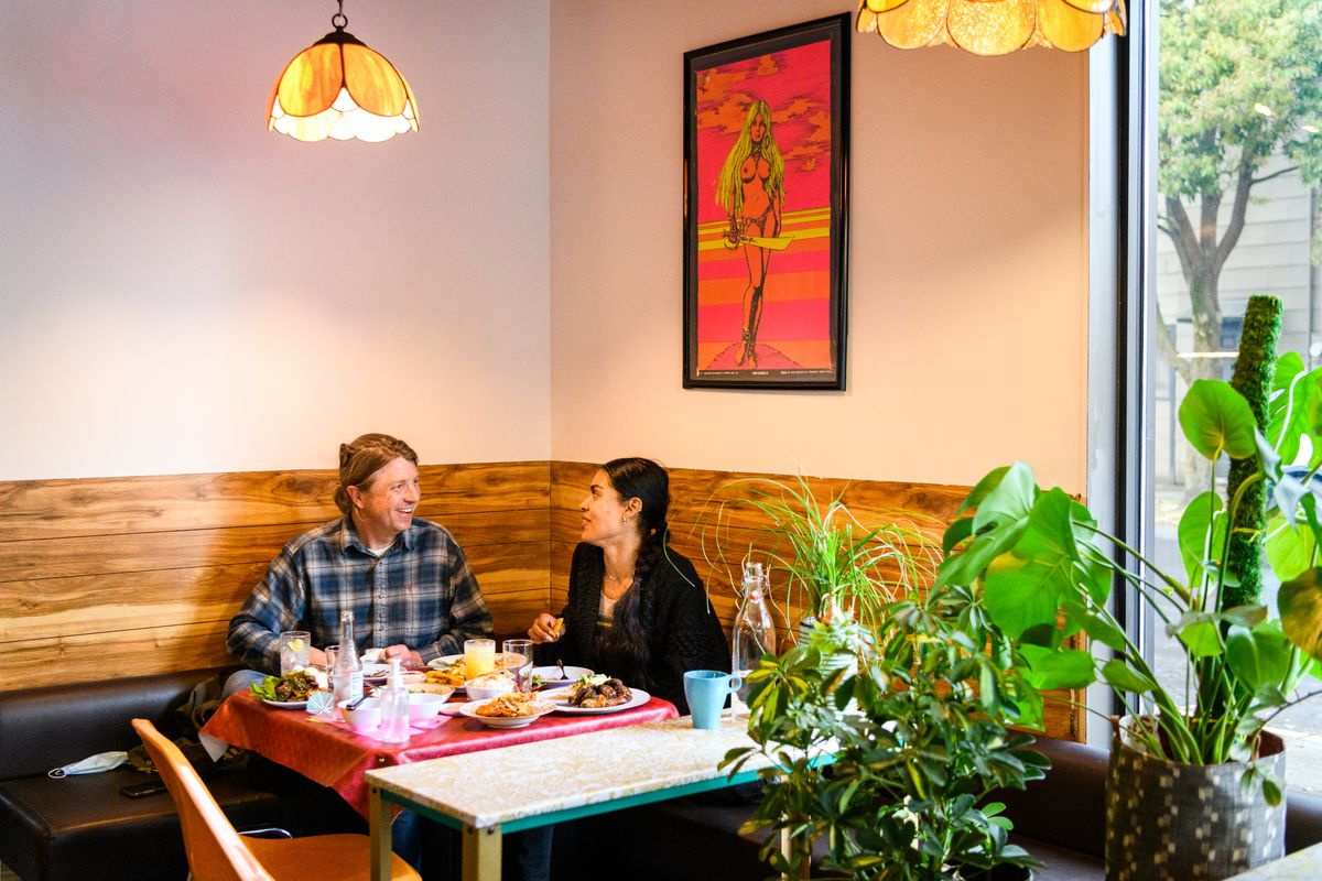 Two people sit at a table covered with food, next to a few plants. Above them, a poster of a naked woman — likely inspired by the film Heavy Metal —hangs on the wall.