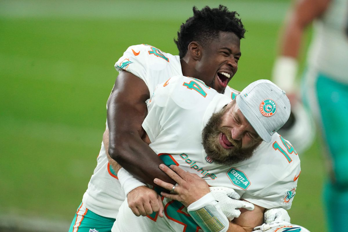 Miami Dolphins quarterback Ryan Fitzpatrick (14) celebrates with wide receiver Isaiah Ford (84) after the game against the Las Vegas Raiders at Allegiant Stadium.