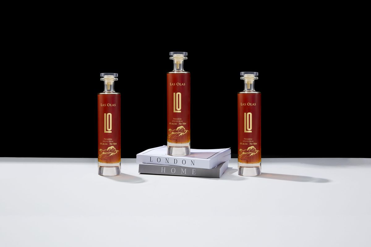 Three bottles of Las Olas spiced rum on a white and black background