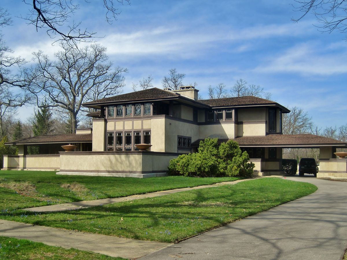 The Willits House by Frank Lloyd Wright. The facade is ivory with dark brown framing. There is a green grass lawn in front of the house.