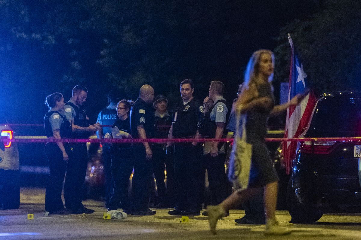 A woman walks by as Chicago police work the scene where 2 people were shot including a 24-year-old man who was shot and killed, in the 3200 West Division St. in the Humboldt Park neighborhood, Saturday, June 19, 2021.