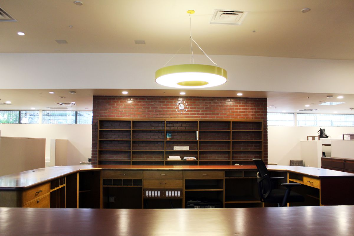 A large wood desk in a U-shape in front of a brick wall with wood bookshelves.