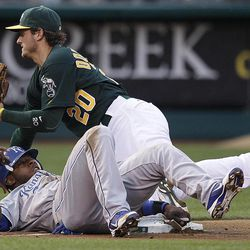 Kansas City Royals' Jason Bourgeois, bottom, is tagged out by Oakland Athletics third baseman Josh Donaldson (20) during the first inning of a baseball game Monday, April 9, 2012, in Oakland, Calif. Bourgeois was attempting to advance on a sacrifice fly hit by Lorenzo Cain.