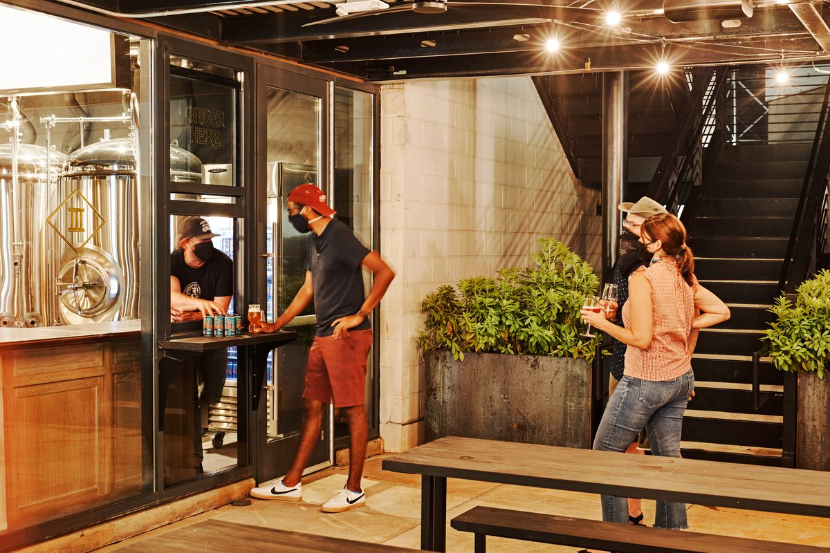 Three Taverns Imaginarium takeout window with a person in mask ordering a six pack of beer from the employee in a black mask and trucker hat. A man and woman stand behind him socially distanced with beers