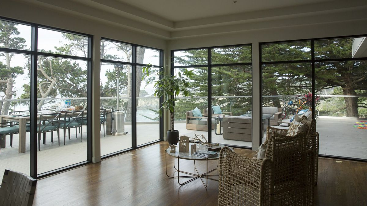 A room from Celeste Wright's home in Big Little Lies features floor-to-ceiling glass windows and views out to a dining room and couch on the patio.
