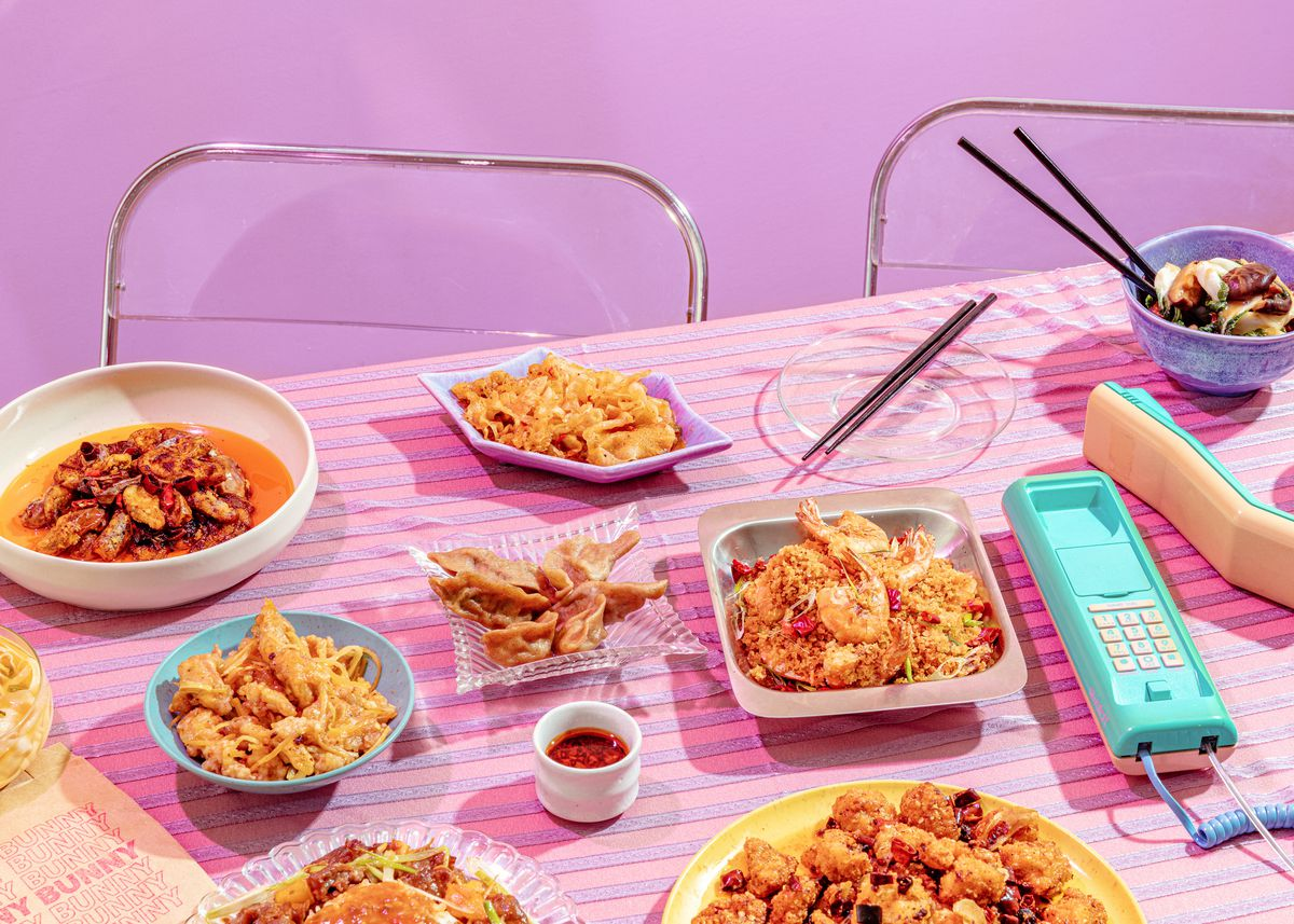 Dishes on a retro, 1980s-styled table with dishes from Bunny Bunny surrounded by silver and clear plastic chairs and a pastel-colored corded phone.