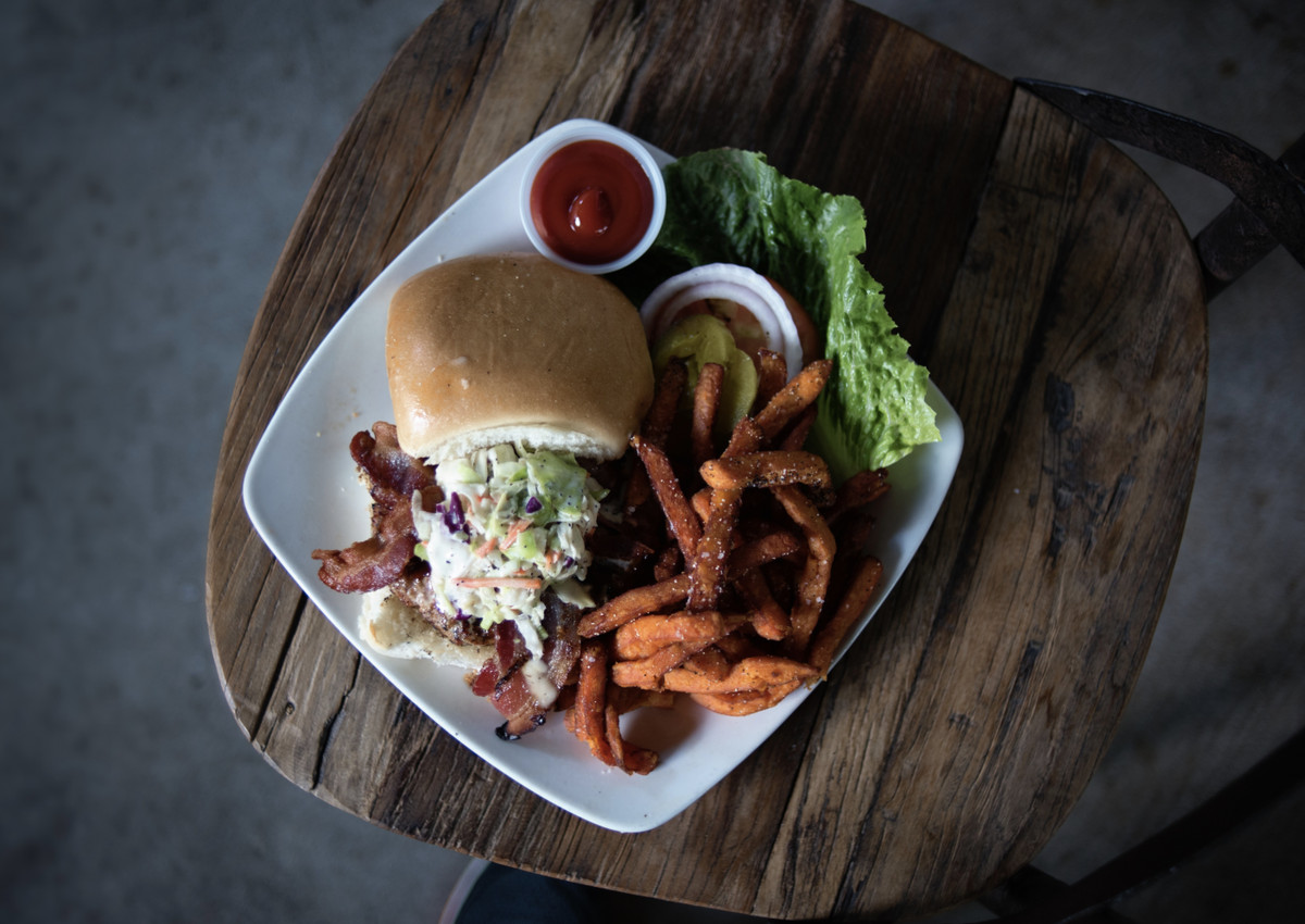 A burger on a plate on a wooden table.