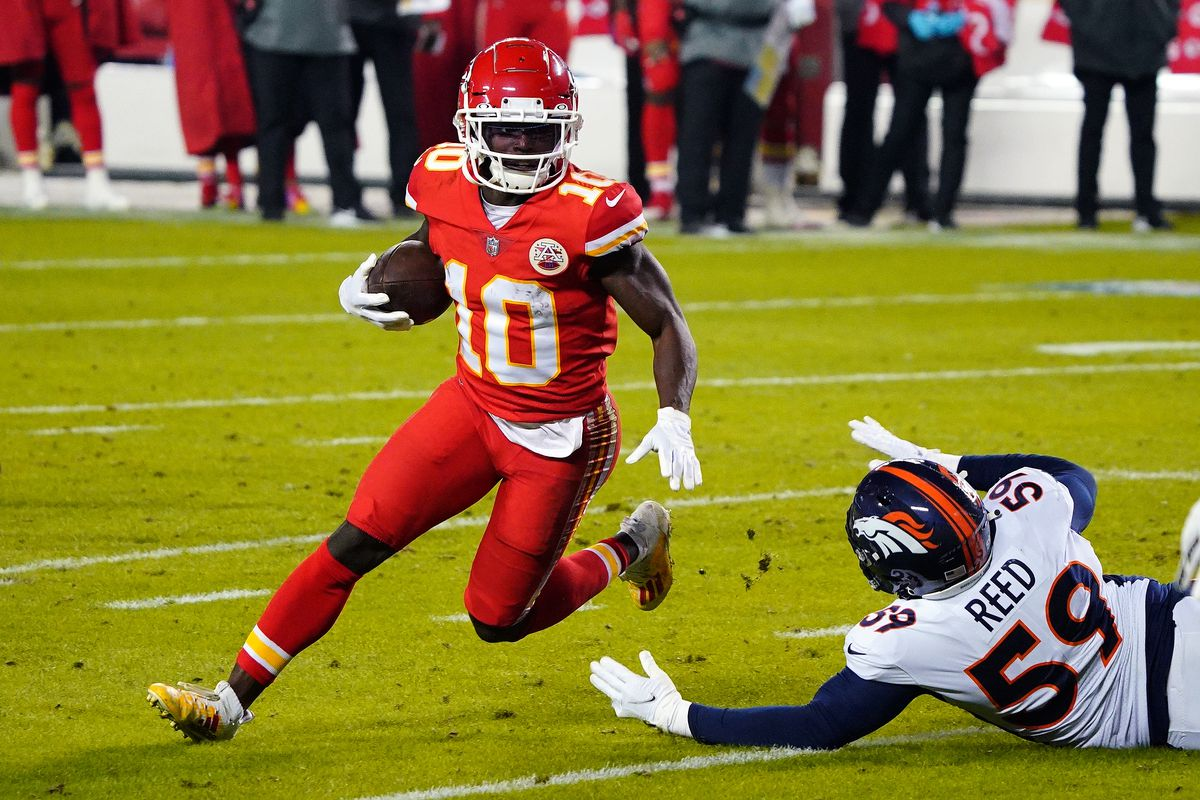 Kansas City Chiefs wide receiver Tyreek Hill (10) runs with the ball past Denver Broncos linebacker Malik Reed (59) during the first half at Arrowhead Stadium.