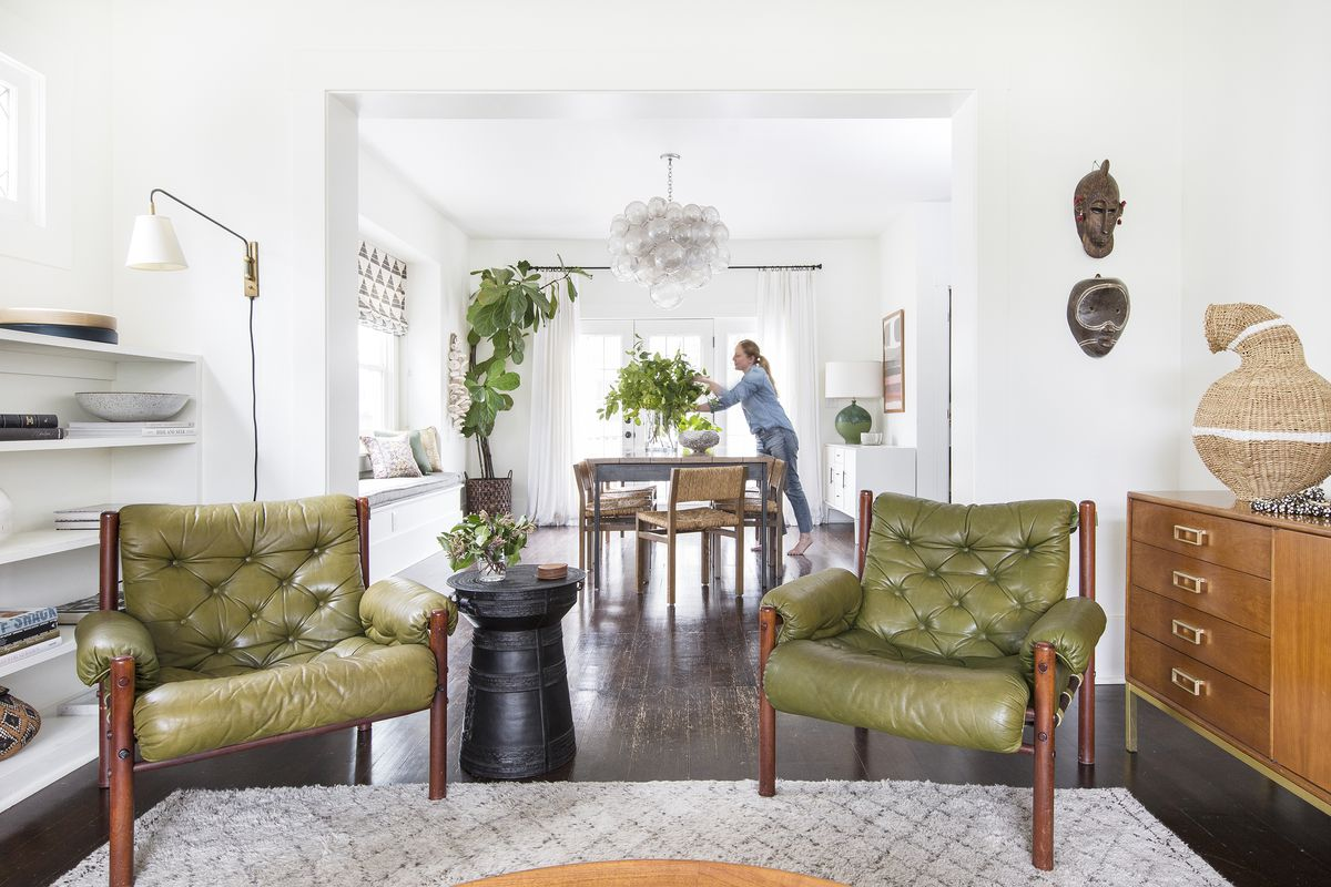 A living room area that looks into a dining area. There are two green armchairs and a patterned area rug. The floor is hardwood. There is a light fixture hanging over a dining room table. A woman arranges flowers in a vase at the dining room table.
