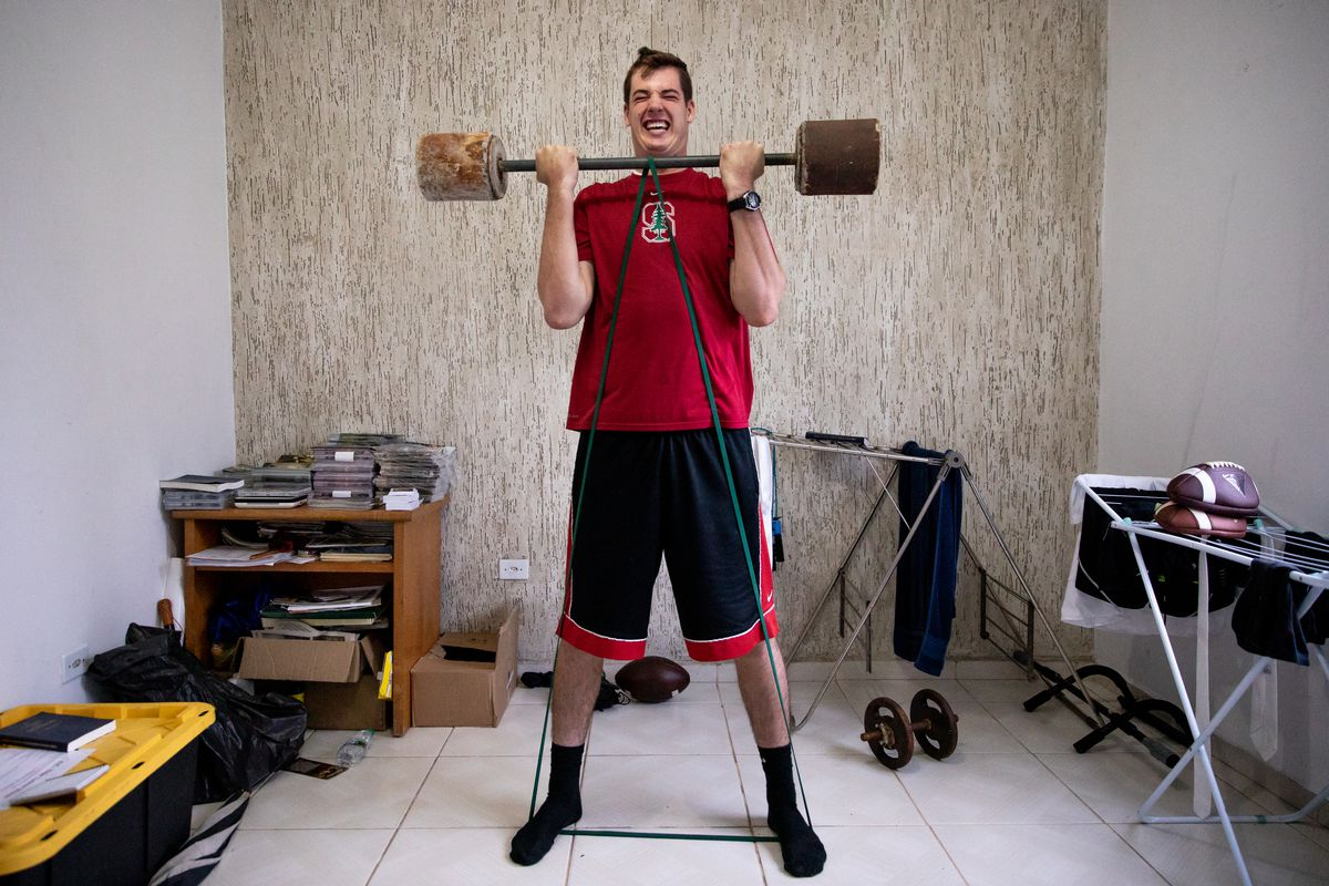 Elder Tanner McKee, a missionary for The Church of Jesus Christ of Latter-day Saints, works out in his home in Paranaguá, Brazil, on Monday, June 3, 2019. McKee has had to be creative to keep up his workout regimen while on his mission. Here, he uses a makeshift barbell with blocks of concrete on each end, plus a resistance band under his feet.