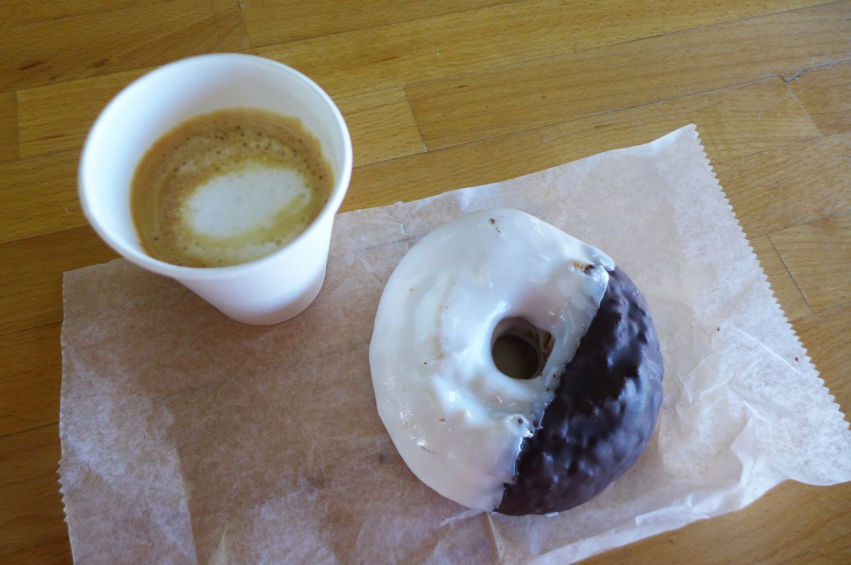 A foamy cortado coffee on the upper left, on the upper right a doughnut with half white and half black frosting.