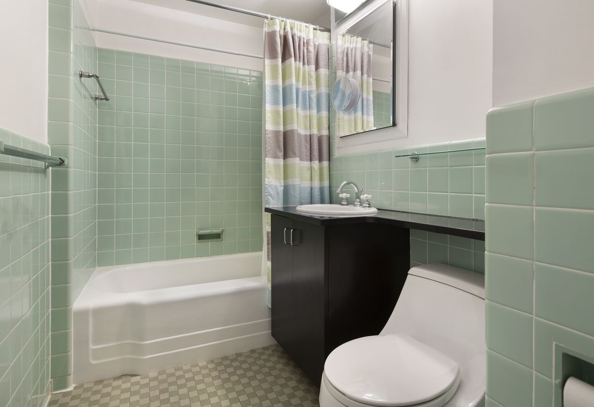 A bathroom with light green tiles.
