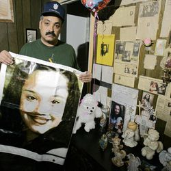 In this Friday, March 3, 2004 file photo shows Felix DeJesus, holding a banner showing his daughter's photograph, standing by a memorial in his living room in Cleveland. Cleveland police say two women who went missing as teenagers about a decade ago have been found alive in a residential area about two miles south of downtown.