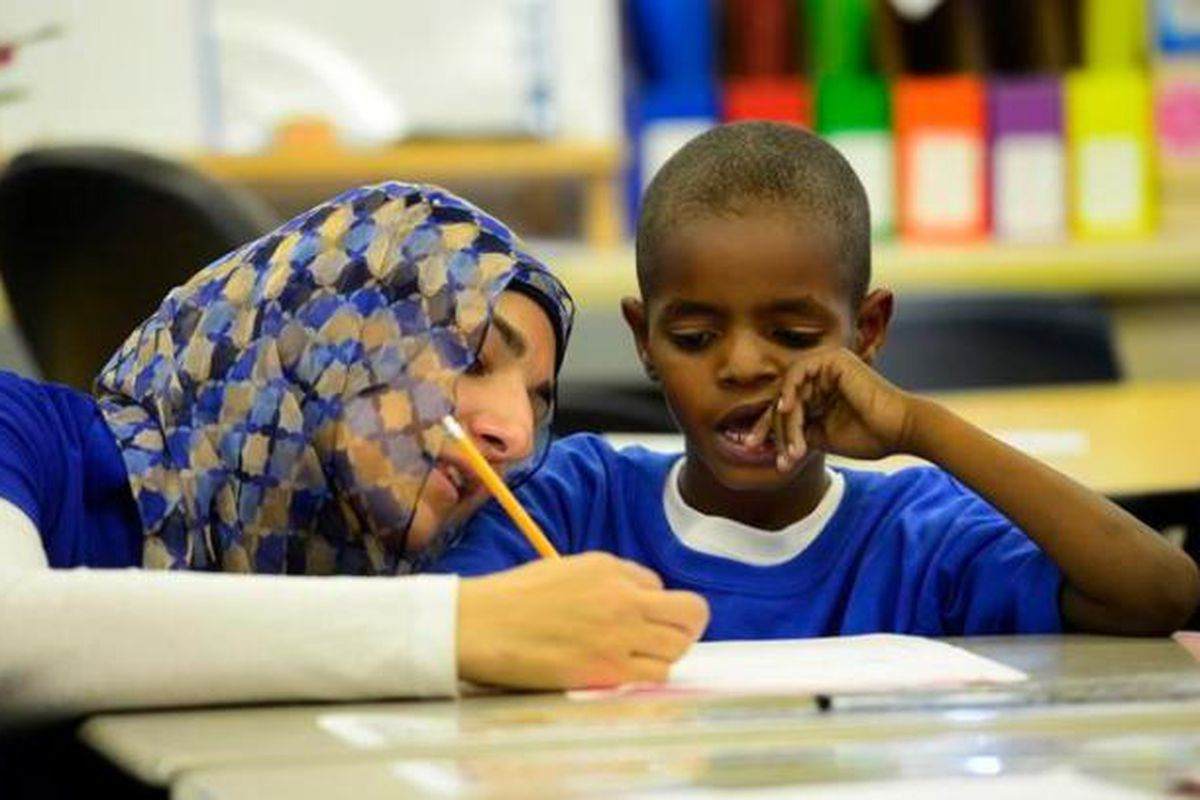 Merhan Zeina, a second-grade teacher at McMeen Elementary in Denver, helps Ahmed Abdelhadi, 8, write a number story.