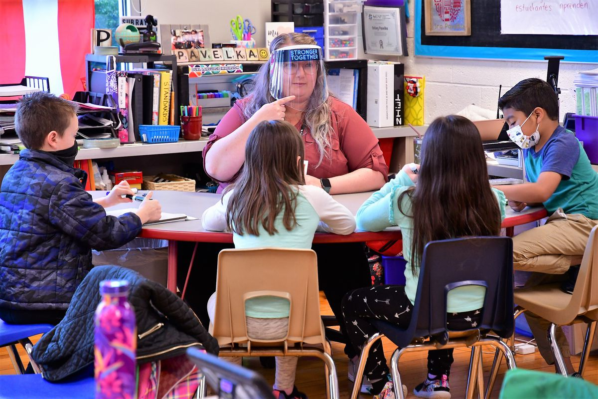 A teacher sits at a table facing four students. The teacher wears a clear plastic face shield and points to her chin.