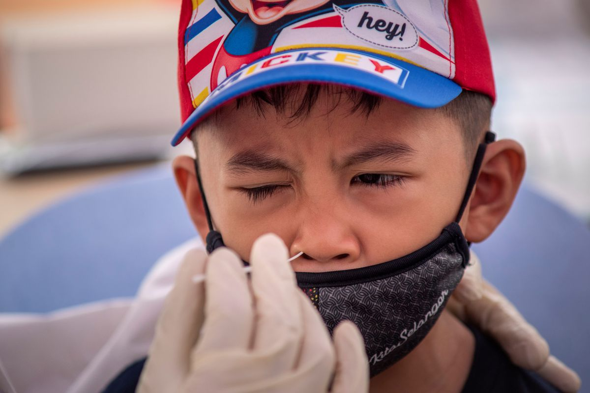 A child winces as he gets swabbed for a COVID test. He's wearing a baseball hat and mask.