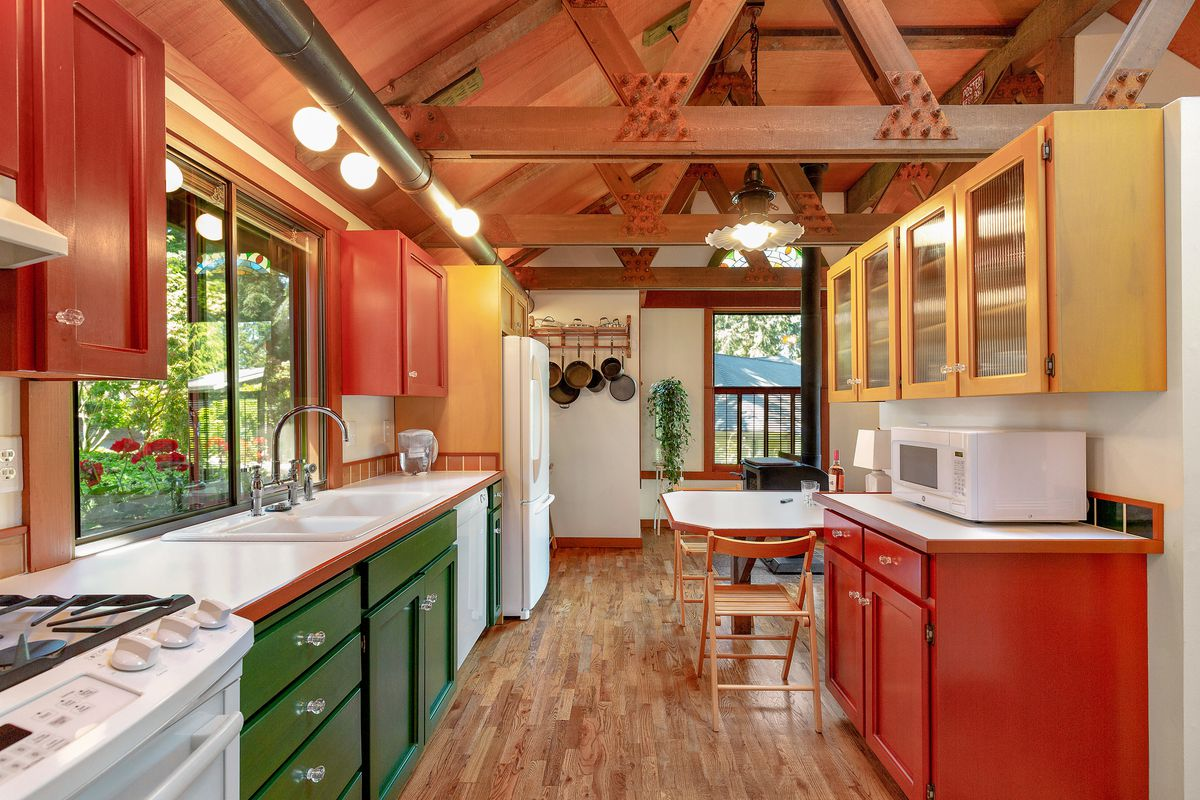 A kitchen has red and green cabinets, white countertops, exposed steel trusses, and a small white table.
