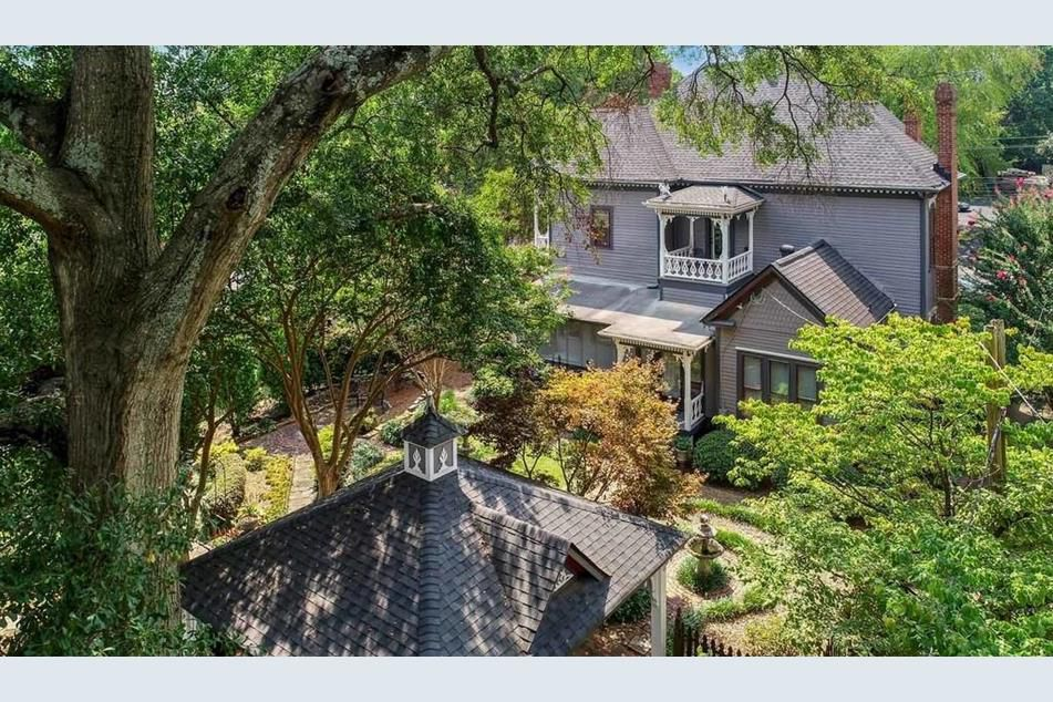 A drone image of a backyard with many trees and ornate gingerbread work seen on back of the home.