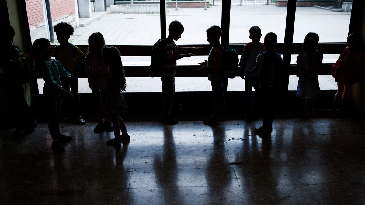 A large group of students speak together in a hallway, silhouetted against a window.