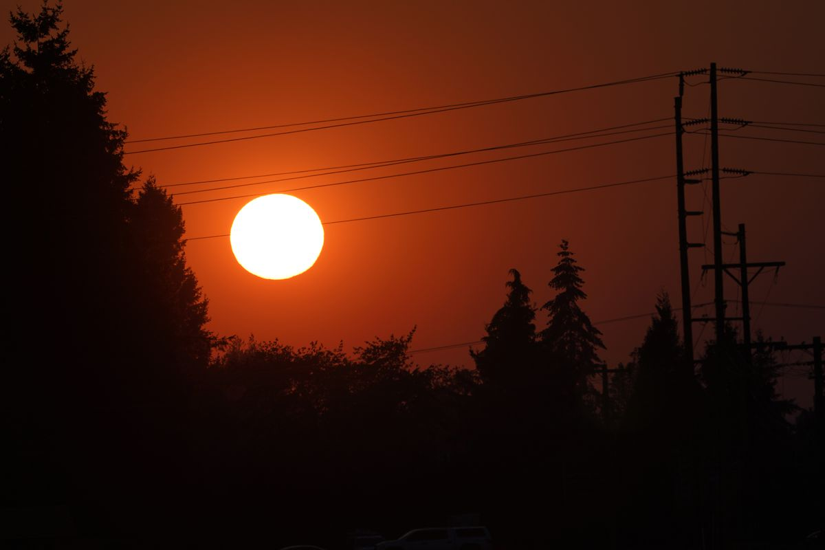 The sun is seen against a sky turned orange with smoke from wildfires as it sets, Tuesday, Sept. 8, 2020, near Sumner, Wash., south of Seattle.