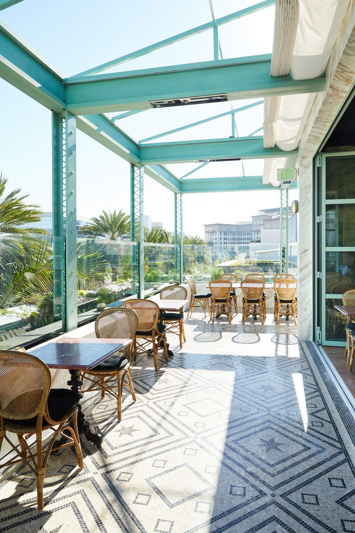 Terrace patio with wicker chairs and marble tables in Beverly Hills' Gucci Osteria.