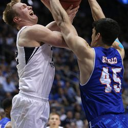 Brigham Young Cougars forward Eric Mika (12) is fouled by Texas-Arlington Mavericks forward Jorge Bilbao (45) as BYU and the University of Texas at Arlington play in NIT basketball action at the Marriott Center in Provo, Utah on Wednesday, March 15, 2017.