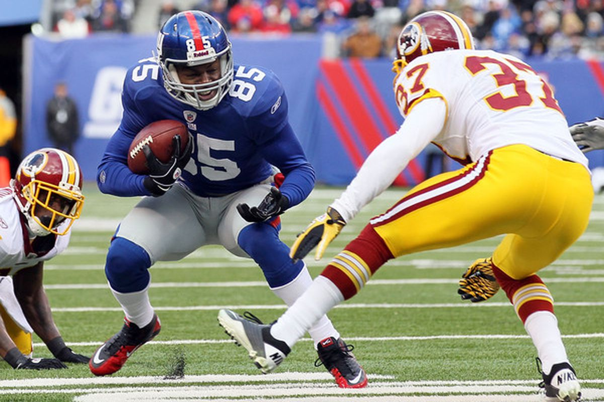 Derek Hagan (85) of the New York Giants runs the ball against Reed Doughty (37) of the Washington Redskins on December 5 2010 at the New Meadowlands Stadium in East Rutherford New Jersey.  (Photo by Jim McIsaac/Getty Images)