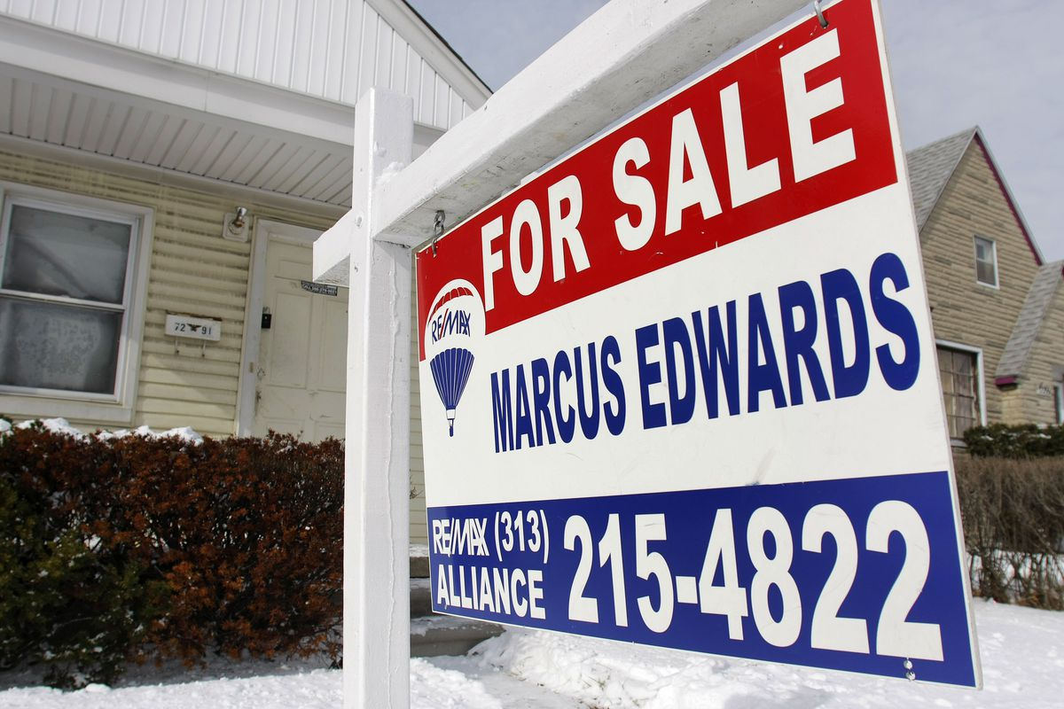 """A large """"for sale"""" sign in front of a house."""