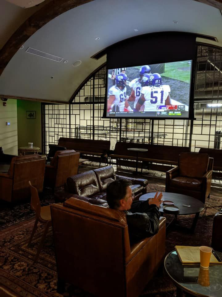 The mezzanine level with couches and a tv showing football game