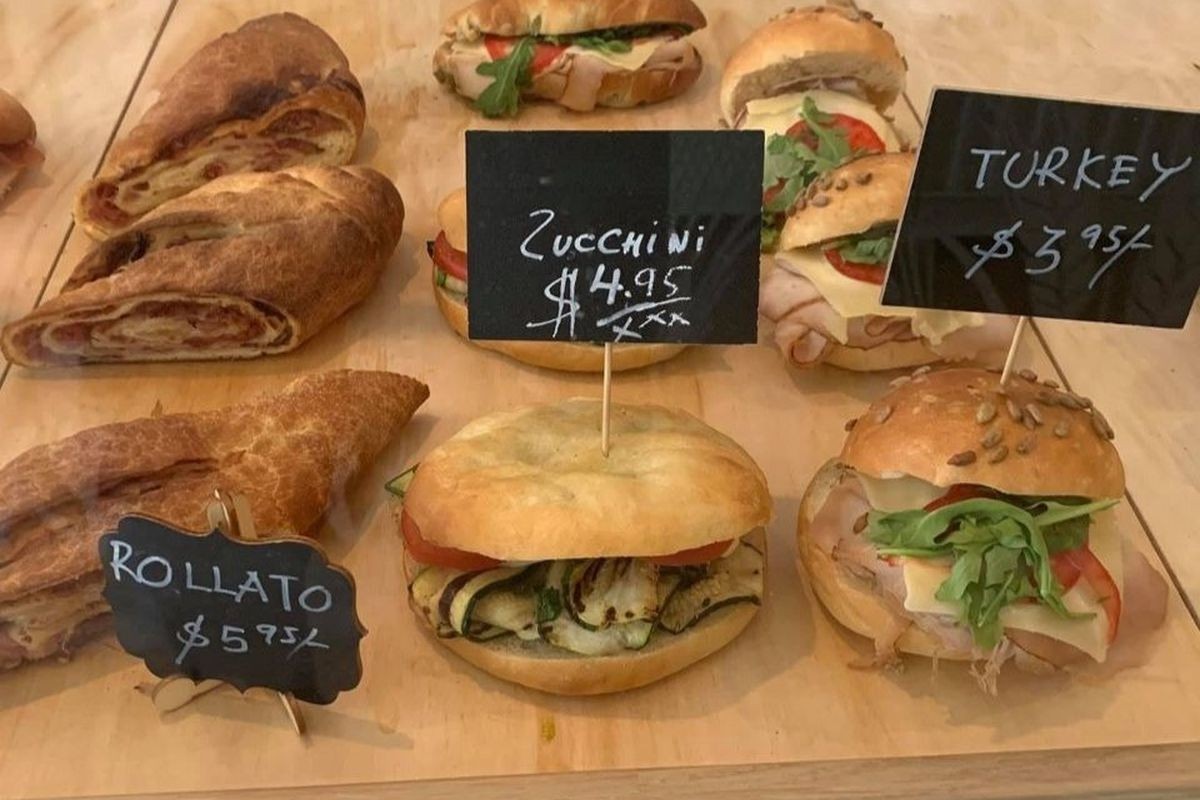 Sandwiches are lined up on a wooden board with black chalk name boards