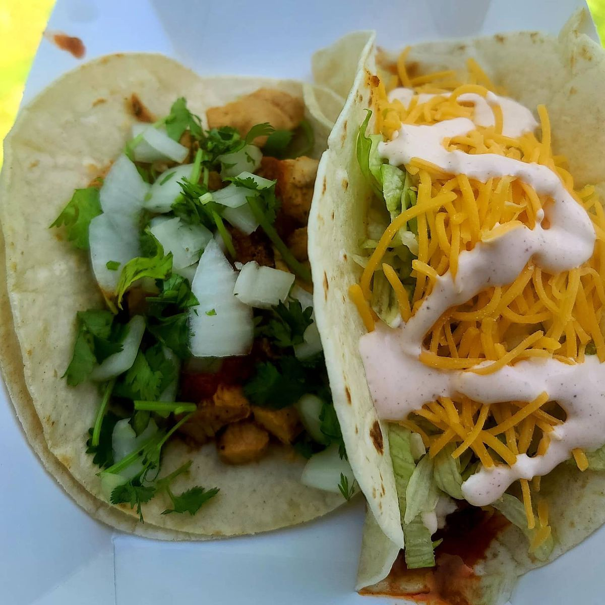 A taco with a corn tortilla, cilantro, and onion, and a flour taco with cheese, lettuce and a creamy dressing.