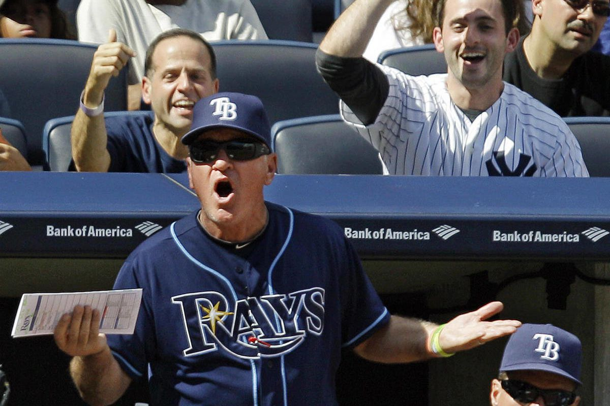 Tampa Bay Rays manager Joe Maddon argues with home plate umpire Paul Emmel from the dugout as pitching coach Jim Hickey watches, lower right, and New York Yankees fans react from their seats, during the third inning of the Rays 6-4 loss in a baseball game