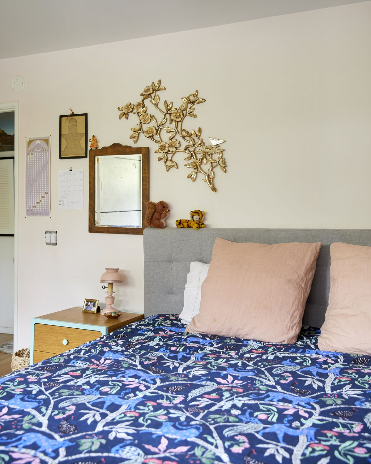 A bedroom with a bed that has patterned bedding and pillows. There is a nightstand to the side of the bed with a lamp. Above the nightstand hangs a mirror and a variety of artwork.