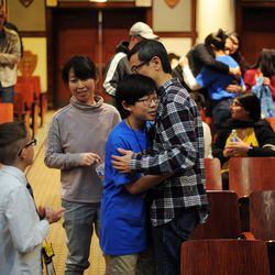 Seventh-grader Aaron Chang(center) from the Audubon Elementary School headed to hug his parents Susanna and Michael Chang after winning annual Citywide Spelling Bee Championship at the Lindblom Math and Science Academy on March 14, 2019. | Victor Hilitski/For the Sun-Times