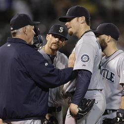 Seattle Mariners' Blake Beavan, second from right, listens to pitching coach Carl Willis during the fifth inning of a baseball game against the against the Oakland Athletics on Friday, Sept. 28, 2012, in Oakland, Calif.