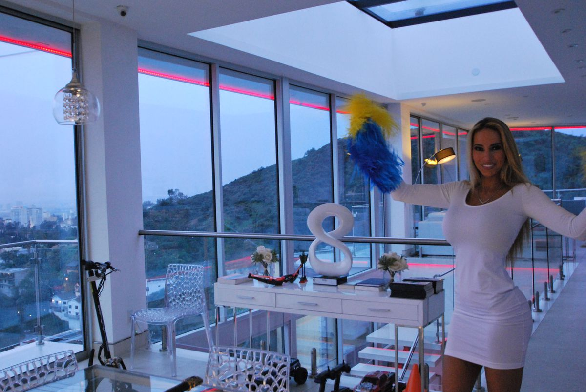 Maria Yotta stands with pom poms near huge windows and a skylight in her very modern home.