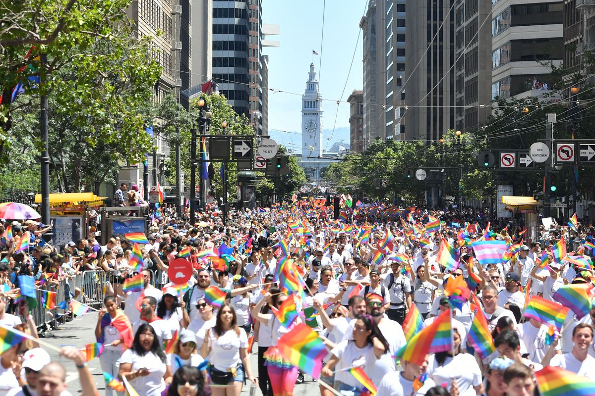 A crowd of people marching and waving rainbow flags during San Francisco's pride parade in 2019.