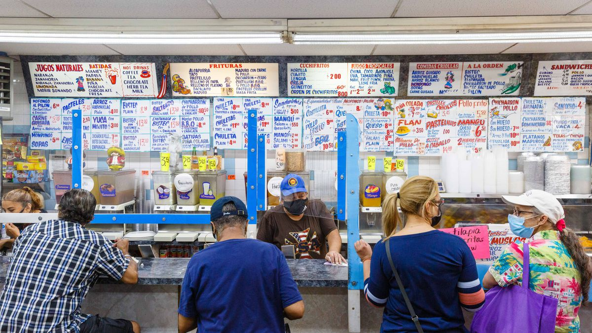 Patrons gather behind a plexiglass guard at a counter for lunch; decorative handwritten menu signs hang in the background