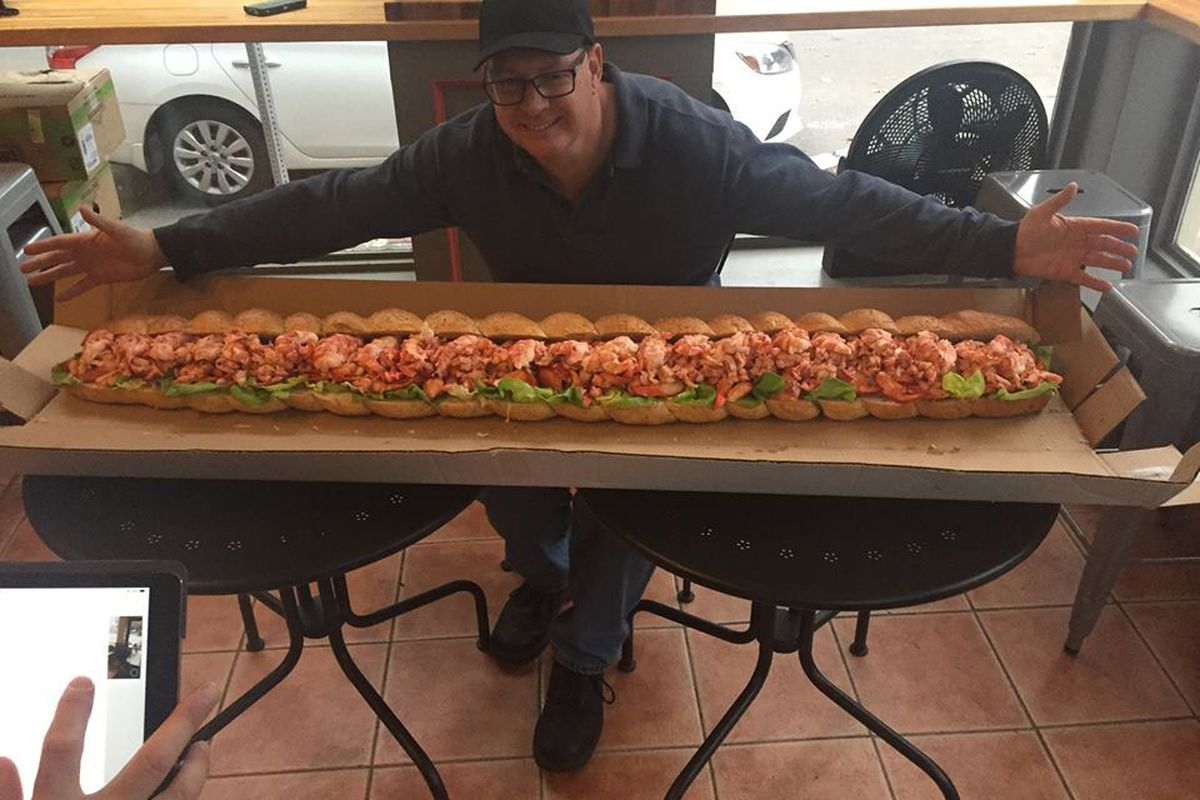 A man stands behind a giant five-foot-long lobster roll, arms outstretched to show off the length of the sandwich. It is sitting on a giant piece of cardboard spread across two small round tables.