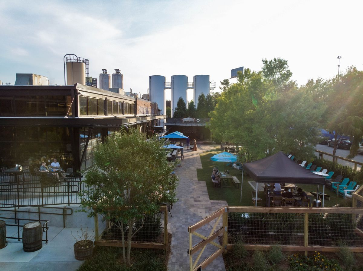 A shot of the patio and lawn area with shade trees, grass, tables with blue umbrellas, and lawn chairs at Sweetwater Brewing
