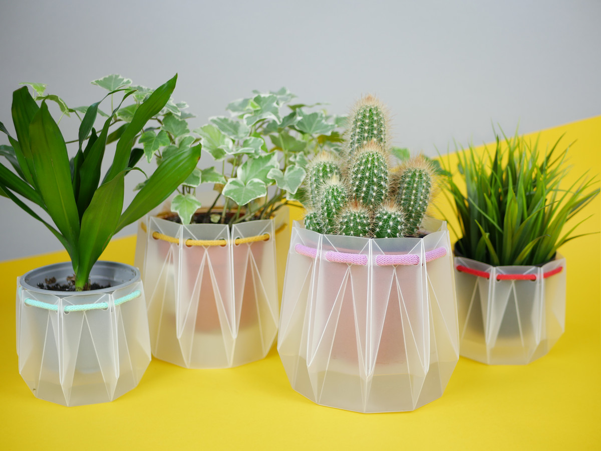 A variety of folded plastic planters with houseplants inside.