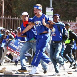 An injured opposition party Democratic Alliance (DA) supporter is helped by fellow members after being hit by a stone during their protest march against the Congress of South African Trade Unions (Cosatu) for opposing the youth wage subsidy in Johannesburg, South Africa on Tuesday May 15, 2012. An opposition party march in Johannesburg turned violent after union supporters hurled rocks at the leader of South Africa's main opposition party.